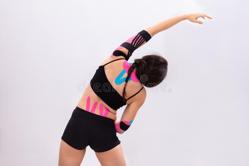 Mujer que estira los brazos con la cinta fisia en su parte posterior imagen de archivo