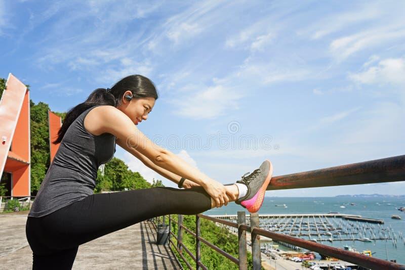 Mujer que estira su pierna antes antes de correr imagenes de archivo