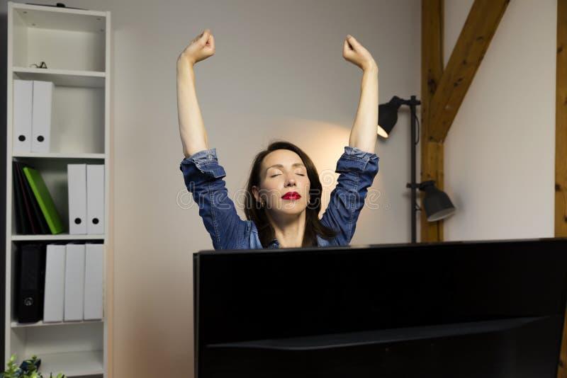 Mujer que estira sus brazos que se sientan por la tabla en el trabajo al lado de c fotografía de archivo libre de regalías