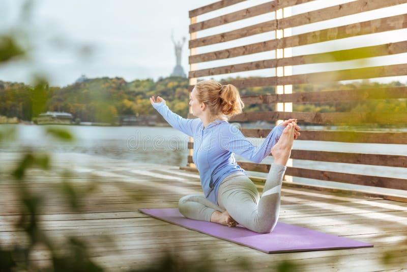 Mujer que estira sus músculos después de hacer ejercicios de la mañana imagenes de archivo