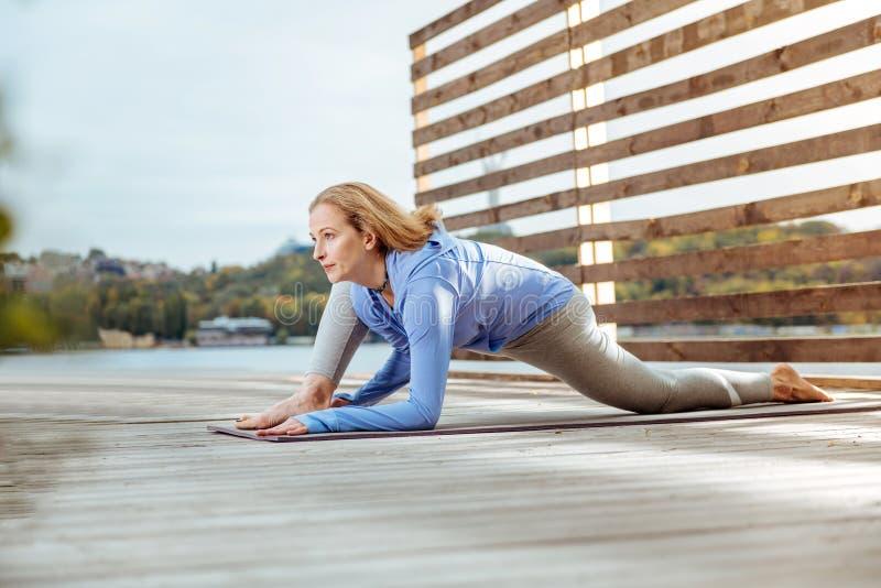 Mujer que estira sus músculos después de hacer ejercicios de la mañana fotos de archivo libres de regalías
