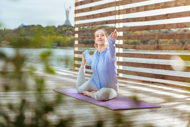 Mujer que estira sus músculos mientras que hace ejercicios de la mañana fotografía de archivo