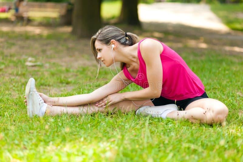 Mujer que estira sus piernas imagen de archivo libre de regalías