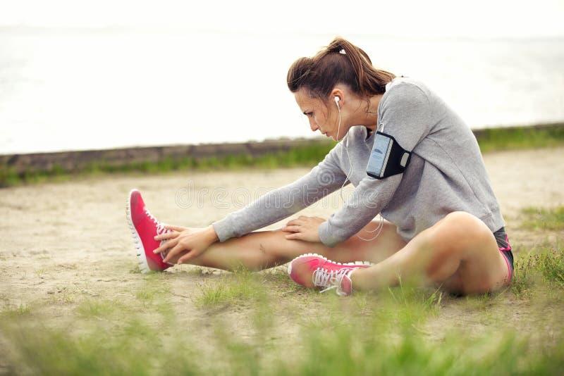 Mujer que estira sus piernas antes de entrenamiento fotografía de archivo libre de regalías