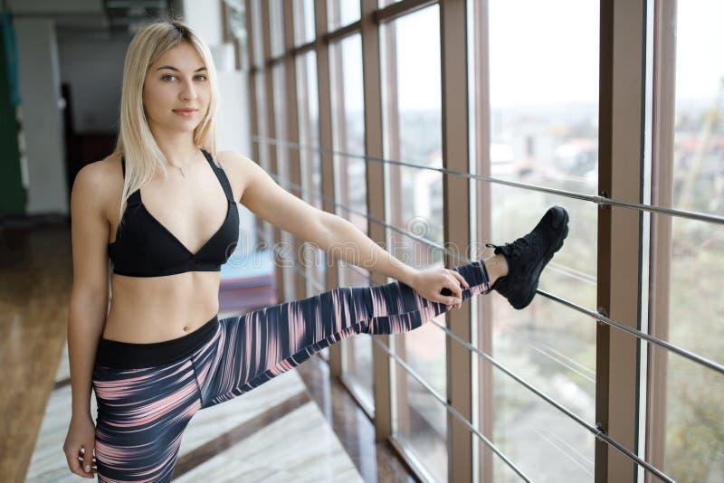 Mujer que estira sus piernas y detrás en el gimnasio Forma de vida activa Deportes en el gimnasio fotografía de archivo libre de regalías