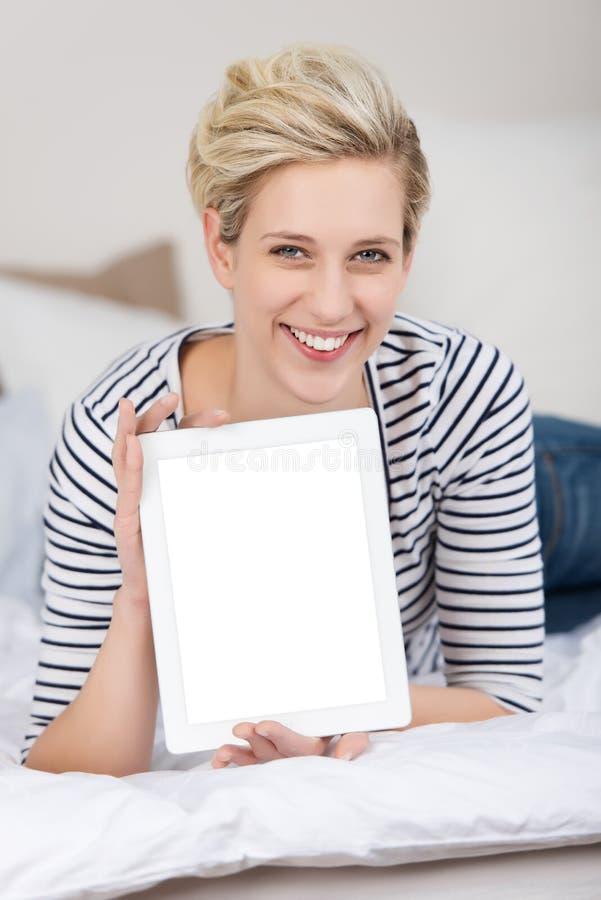 Mujer que exhibe la tableta de Digitaces mientras que miente en cama fotos de archivo libres de regalías
