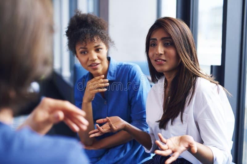 Mujer que explica estrategia empresarial a los compa?eros de trabajo fotografía de archivo