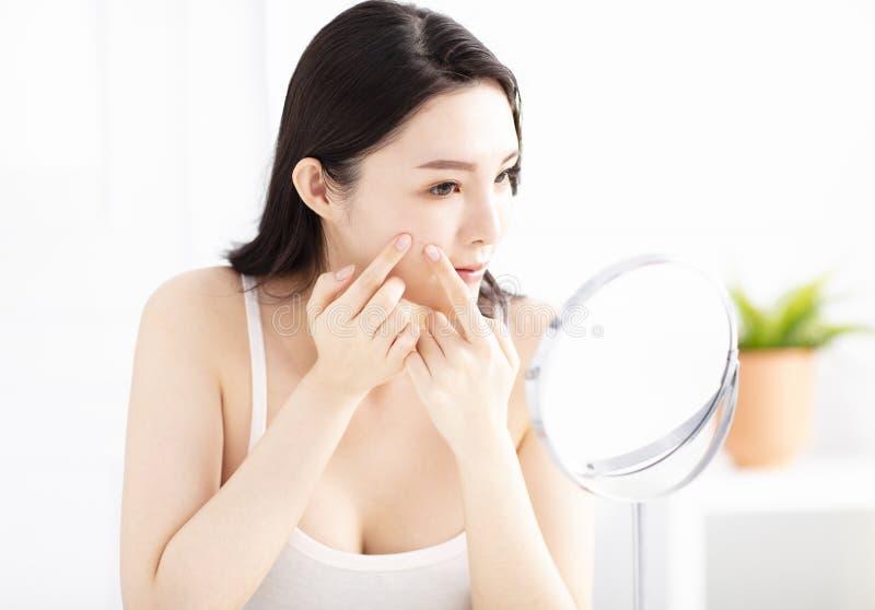 mujer que exprime espinillas delante del espejo foto de archivo