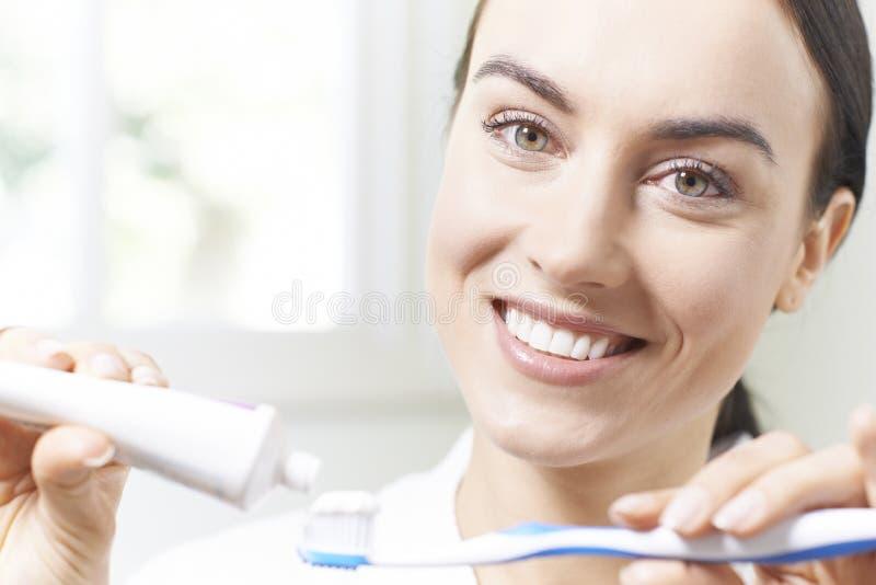 Mujer que exprime la crema dental sobre Tootbrush en cuarto de baño foto de archivo