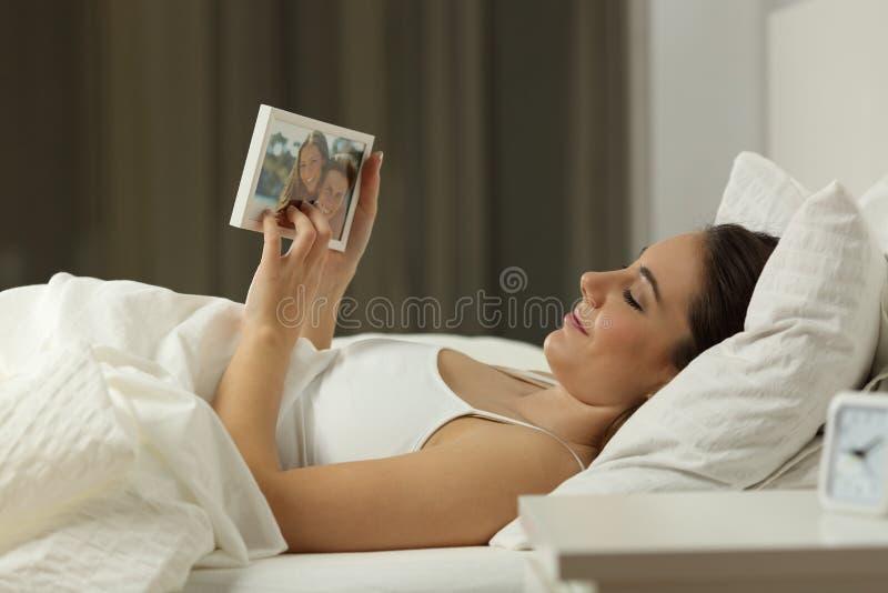 Mujer que falta a su novio en la cama en la noche fotos de archivo