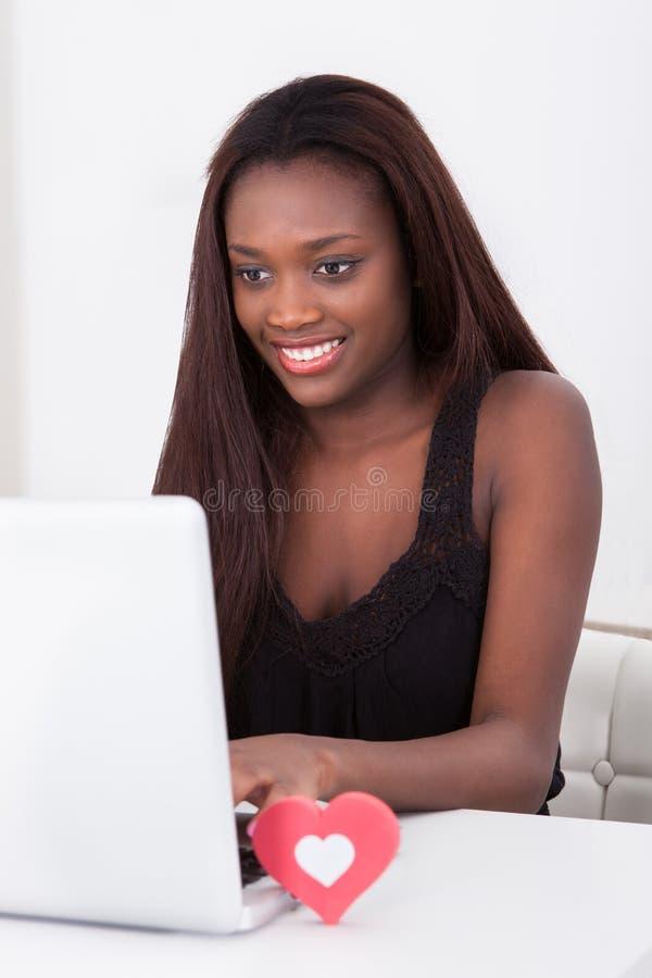 Mujer que fecha en línea en el ordenador portátil en casa fotografía de archivo libre de regalías