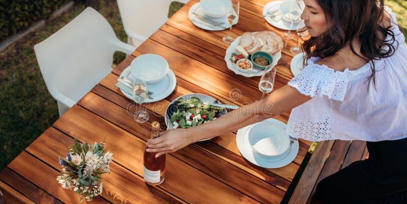 Mujer que fija una mesa de comedor para el estreno de una casa imagen de archivo
