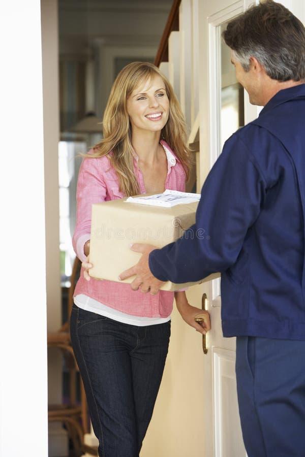 Mujer que firma para el paquete entregado por el mensajero fotografía de archivo