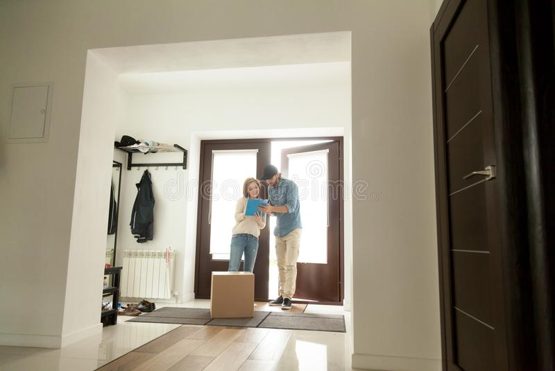 Mujer que firma para el paquete que recibe la caja de mensajero en casa fotos de archivo
