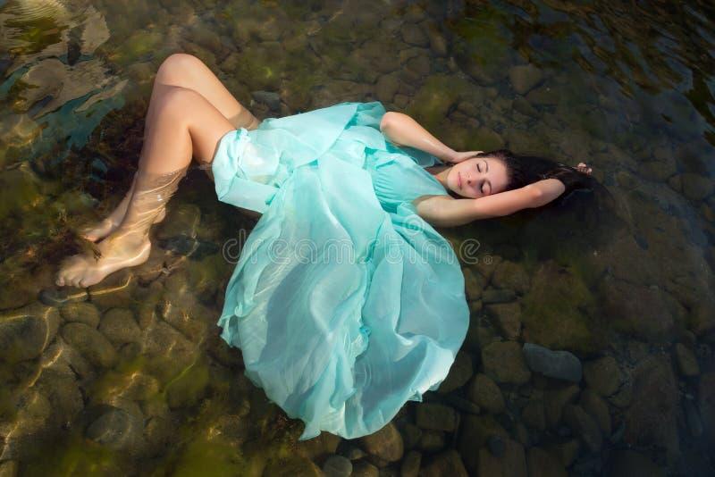 Mujer que flota en aguas de la playa foto de archivo libre de regalías