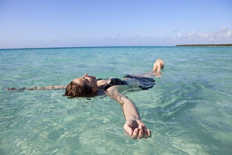 Mujer que flota en el mar imagen de archivo