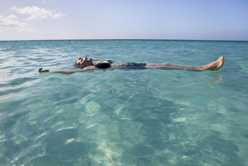 Mujer que flota y que se relaja en el mar fotos de archivo