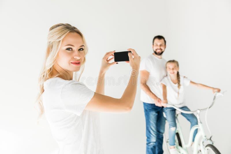 Mujer que fotografía a la familia con smartphone fotos de archivo
