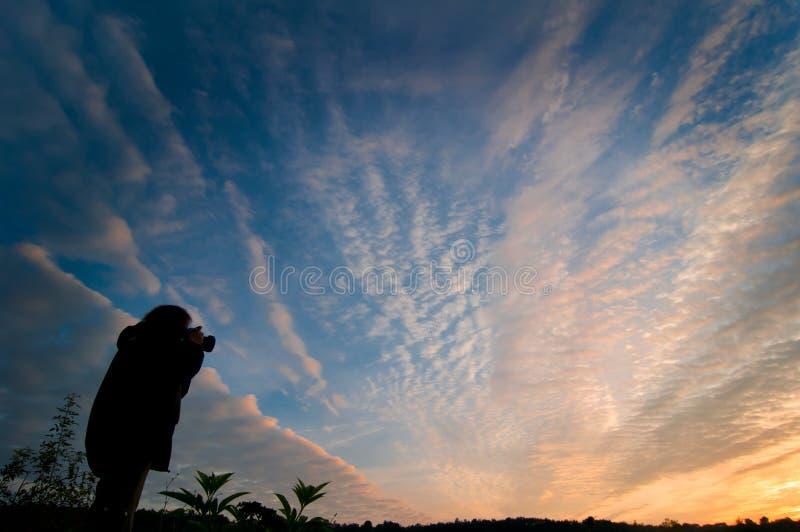 Mujer que fotografía la salida del sol fotos de archivo