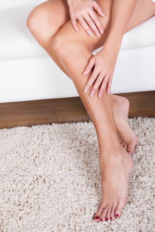 Mujer que frota ligeramente sus piernas desnudas imagen de archivo
