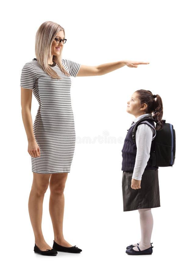 Mujer que gesticula con la mano y que muestra la altura de una pequeña colegiala fotografía de archivo