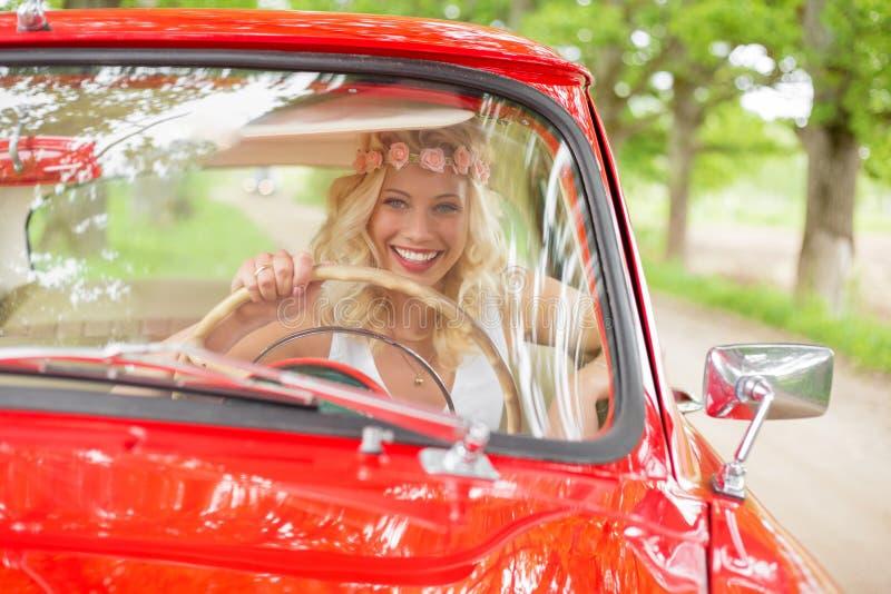 Mujer que goza conduciendo un coche retro rojo imágenes de archivo libres de regalías