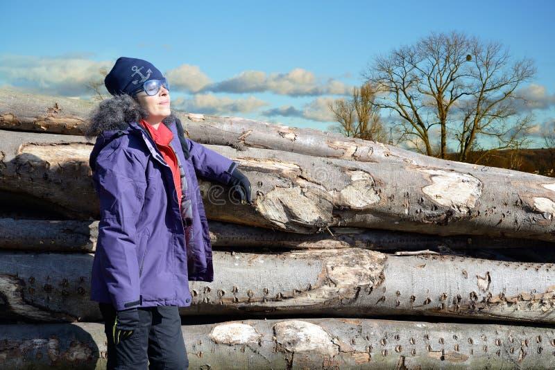 Mujer que goza de la pila cercana al aire libre del sol del invierno de registros foto de archivo libre de regalías