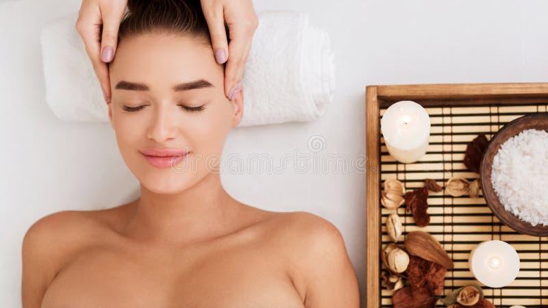 Mujer que goza de masaje de cara y de aromatherapy en salón del balneario imagen de archivo libre de regalías