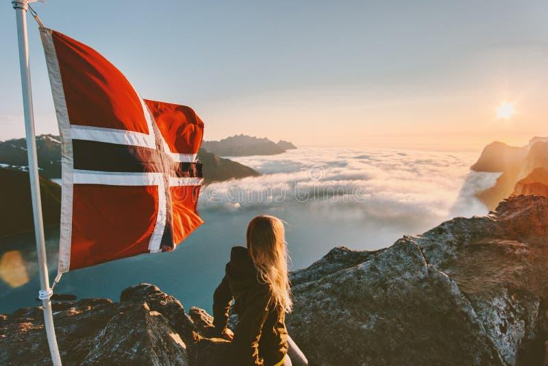 Mujer que goza de Mountain View de la puesta del sol y de la bandera de Noruega en el top fotografía de archivo libre de regalías