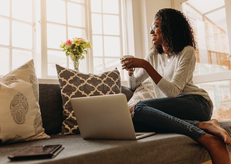 Mujer que goza de una taza de café mientras que trabaja en el ordenador portátil foto de archivo libre de regalías