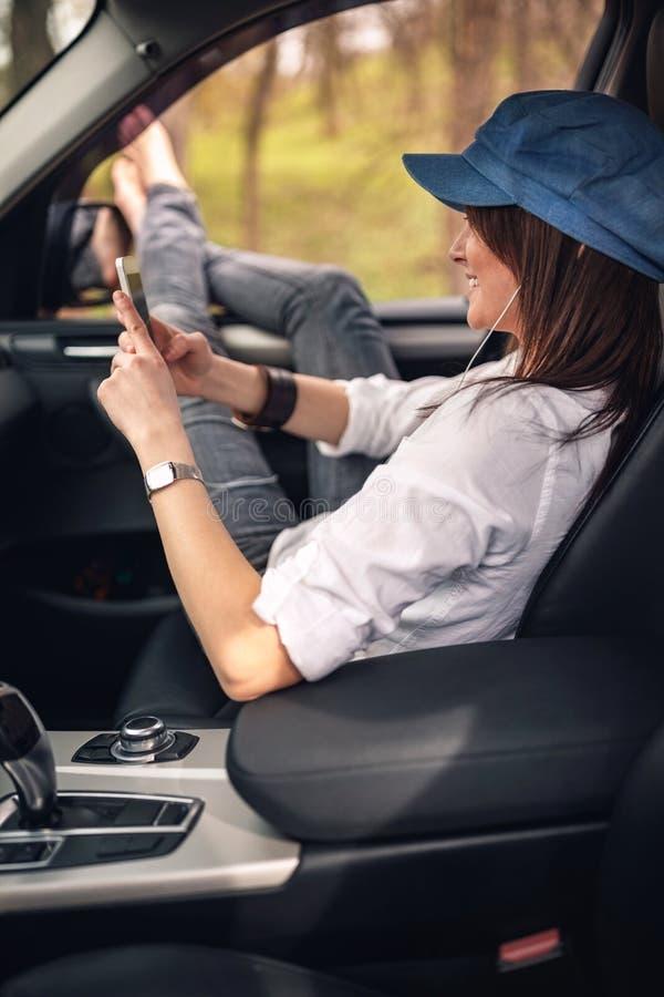 Mujer que goza en un viaje por carretera que escucha la música imágenes de archivo libres de regalías