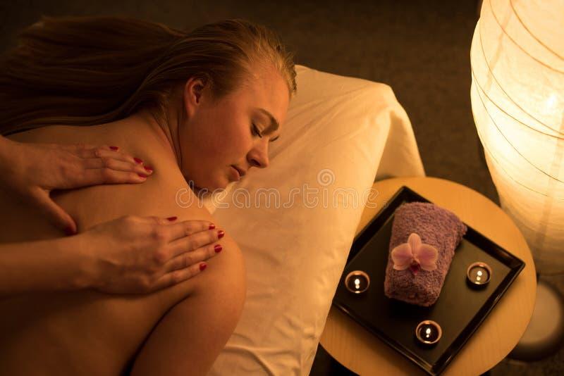 Mujer que goza relajando masaje trasero en centro cosmético del balneario en s foto de archivo