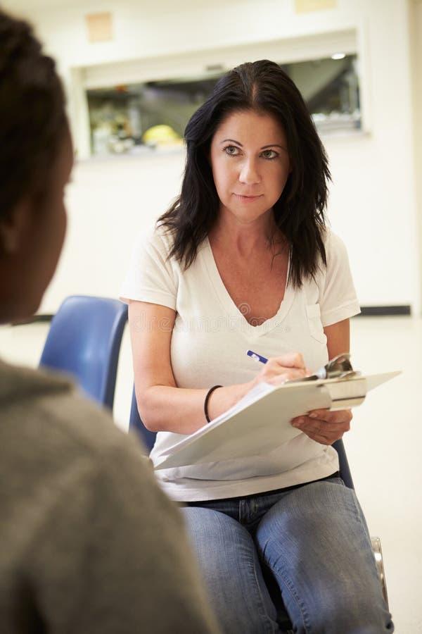Mujer que habla con el consejero que toma notas imagenes de archivo