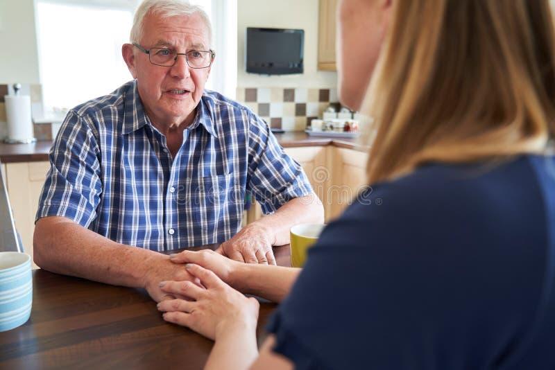 Mujer que habla con el hombre mayor infeliz que se sienta en cocina en casa imagenes de archivo