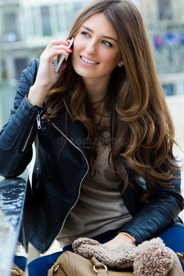 Mujer que habla con el teléfono móvil en la calle foto de archivo