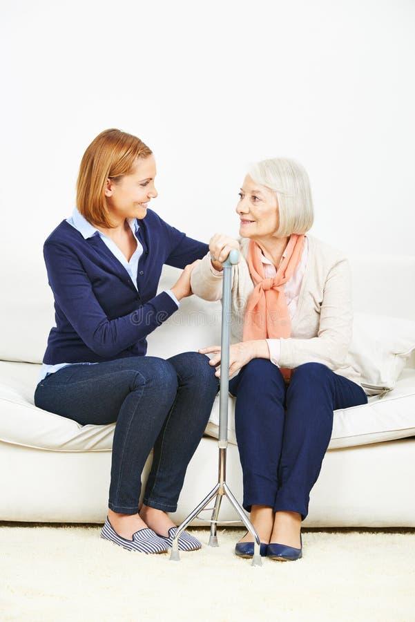 Mujer que habla con la mujer mayor en casa imagen de archivo