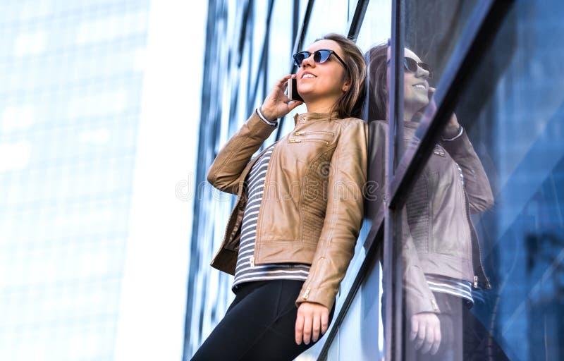 Mujer que habla en el teléfono en ciudad y que se inclina contra el vidrio imagenes de archivo