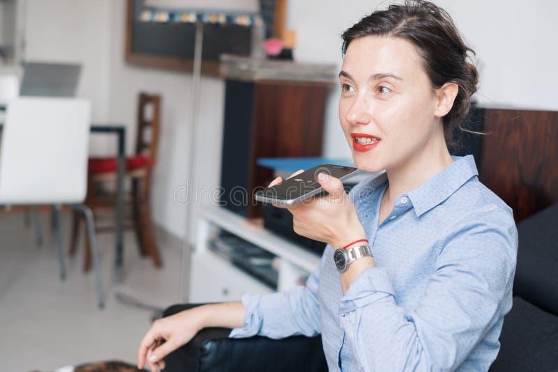 Mujer que habla en el teléfono con el ayudante de la voz digital imagen de archivo libre de regalías