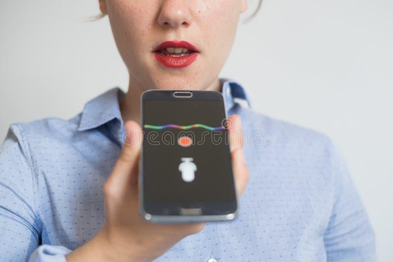 Mujer que habla en el teléfono con el ayudante de la voz digital fotos de archivo