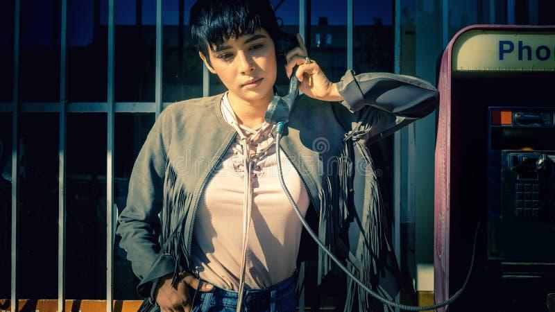 Mujer que habla en el teléfono de pago de la gasolinera imagen de archivo