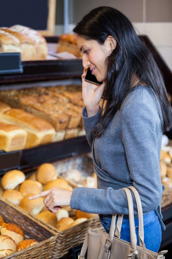 Mujer que habla en el teléfono móvil en el contador del pan imagen de archivo