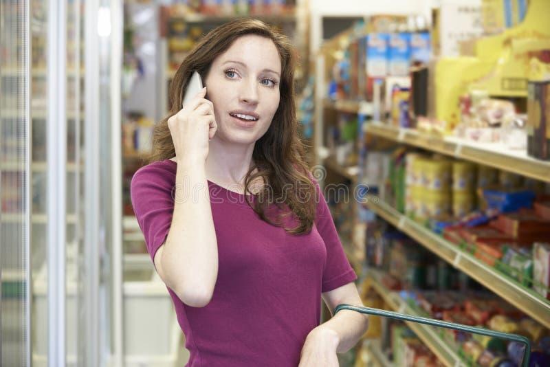 Mujer que habla en el teléfono móvil en supermercado imagen de archivo