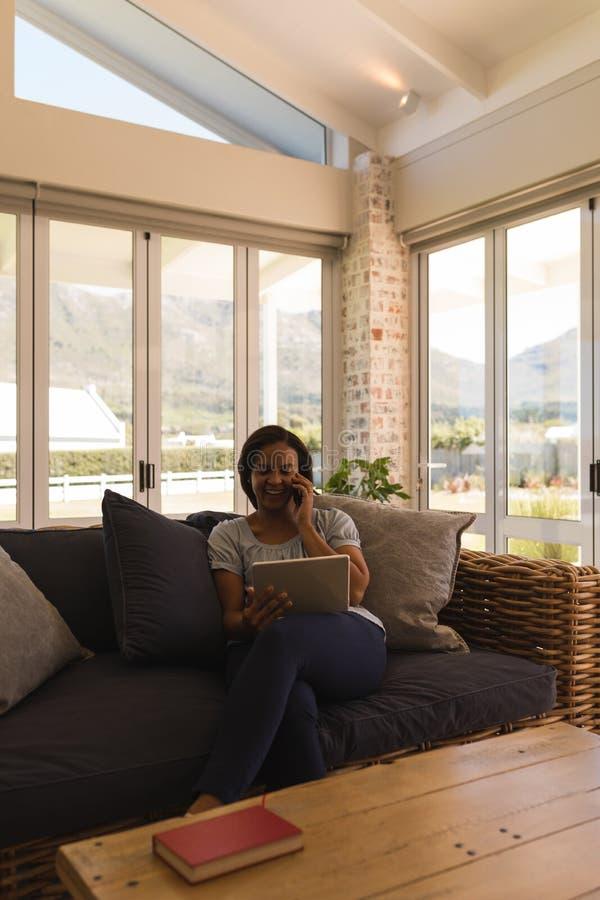 Mujer que habla en el teléfono móvil mientras que usa la tableta digital en sala de estar imagenes de archivo