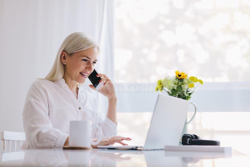 Mujer que habla en el teléfono, usando el ordenador portátil imagen de archivo libre de regalías