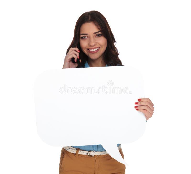 Mujer que habla en el teléfono y que lleva a cabo una burbuja del discurso fotos de archivo libres de regalías