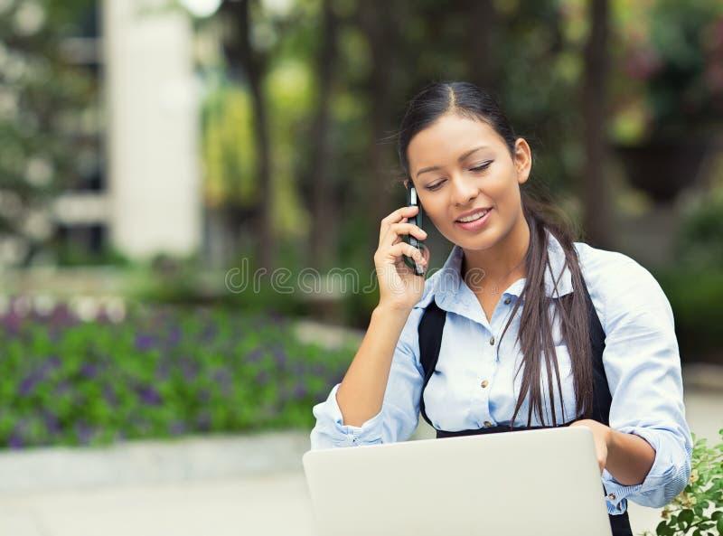 Mujer que habla en un teléfono, mirando en la pantalla del ordenador portátil foto de archivo