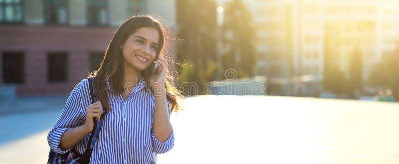Mujer que habla por el teléfono y que sonríe mientras que camina a lo largo de las calles con luz del sol en su cara y espacio de fotos de archivo