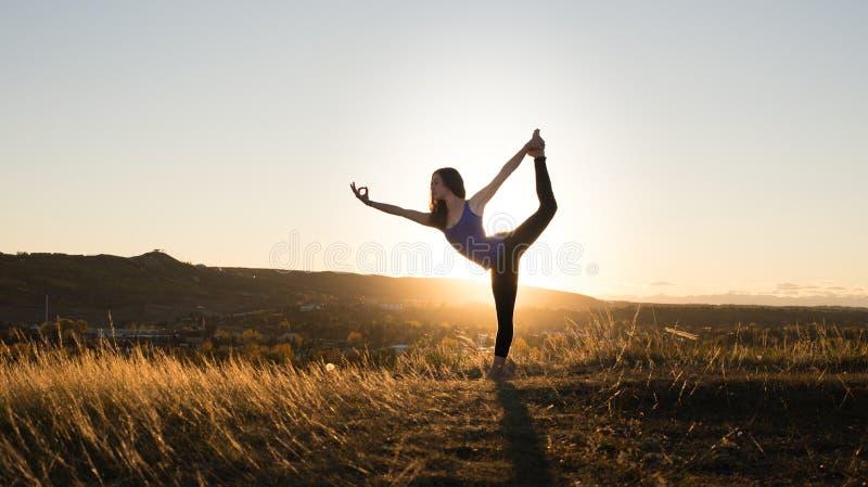Mujer que hace actitud de los bailarines de la yoga durante puesta del sol foto de archivo