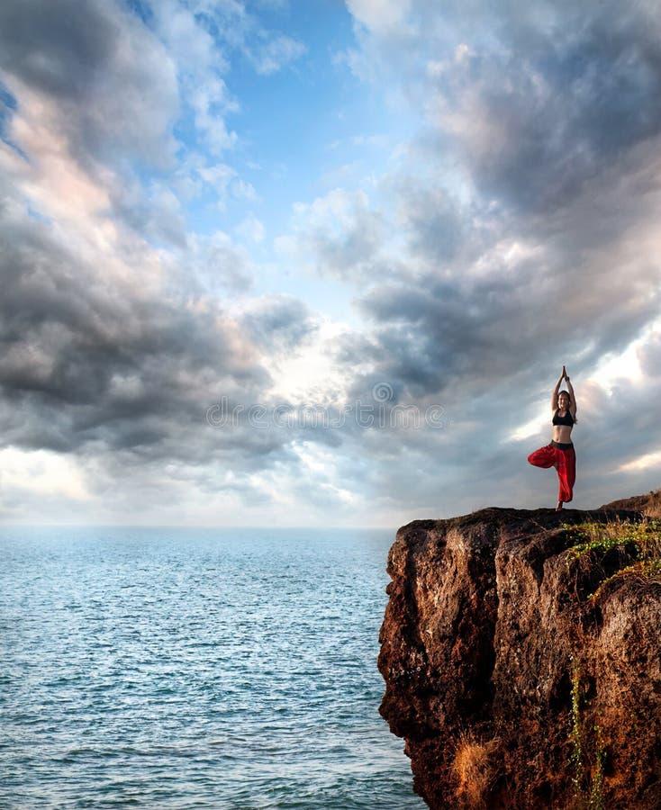 Mujer que hace actitud del árbol del vrikshasana de la yoga fotos de archivo