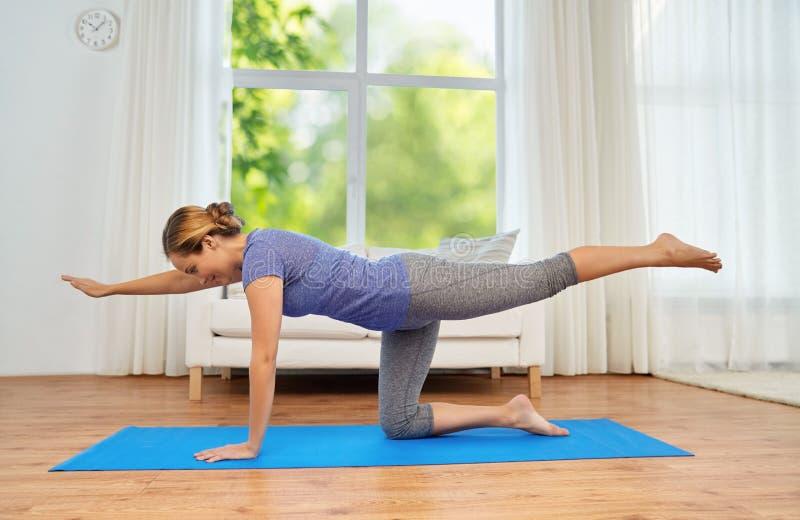Mujer que hace actitud del gato de la yoga en casa imagen de archivo